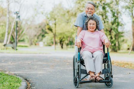 bonne femme asiatique souriante asiatique dans un fauteuil roulant et marchant avec son mari à l & # 39 ; extérieur dans le parc