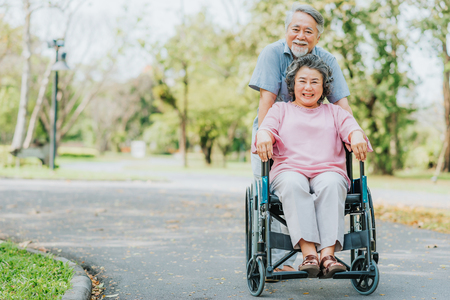 Happy smile Asian senior woman in a wheelchair relaxing and walking with her husband outside at the park