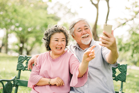Happy senior Asian couple laughing and smiling together while looking at smartphone mobile