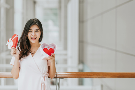 Beautiful happy smiling and cheeful Asian woman holding gift box with red heart inside on valentine day Stockfoto