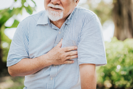 Cropped shot of senior man holding his chest and feeling pain suffering from heart attack outdoor at the park Stockfoto