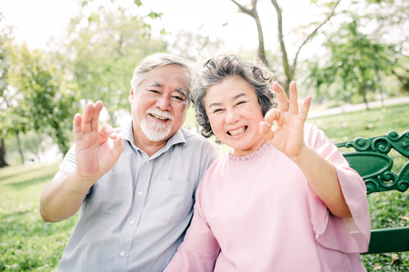 Positive smiing happy Asian senior couple with ok hand sign gesture in the park Stock Photo