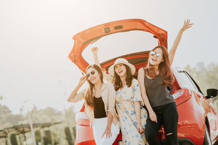 Three happy Asian girl best friends traveler celebrating a good time with arm up while sitting in car trunk  스톡 콘텐츠