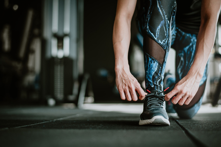 Cropped shot of woman tying her shoelaces before training in the gym