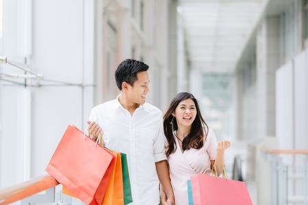 Feliz pareja asiática con coloridos bolsos de compras y disfrutar de las compras, divertirse juntos en el centro comercial. Consumismo, amor, citas, concepto de estilo de vida