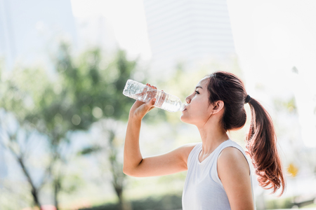 Shot of a young Asian woman drinking water from water bottle after jogging in the park. Stockfoto