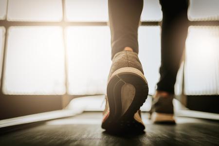 Cierre de tiro de la pierna de mujer corriendo en un gimnasio en una caminadora . fitness entrenamiento y concepto de estilo de vida saludable Foto de archivo - 97138834