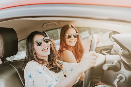 Two happy Asian girl best friends laughing and smiling in car during a road trip to vacation.