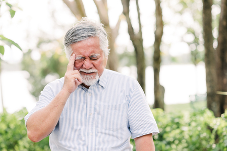 Portrait of Asian senior man sitting in the park suffering from a headache