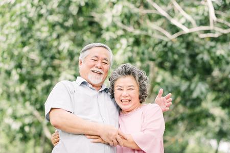 Glückliche asiatische ältere Paare, die eine gute Zeit haben. Sie lachen und lächeln, während sie sich im Freien im Park halten. Standard-Bild
