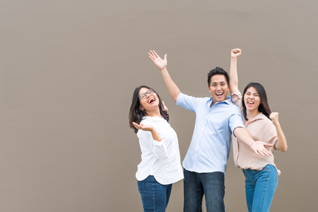 Group of happy three asian friends in casual wear standing laugh and having fun together