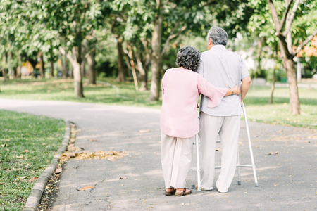 Back view of loving senior couple talking a walk with walker in the park