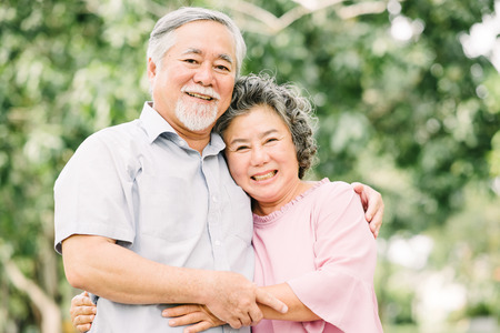 Happy Asian senior couple smiling while holding each other outdoor in the park.