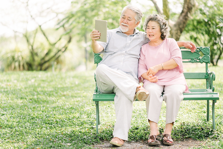 Happy senior Asian couple sitting on the bench using digital tablet together outdoor