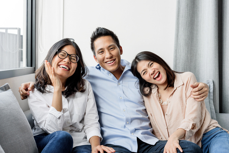 Group of happy three Asian best friends in casual wear laughing and smiling together in living room