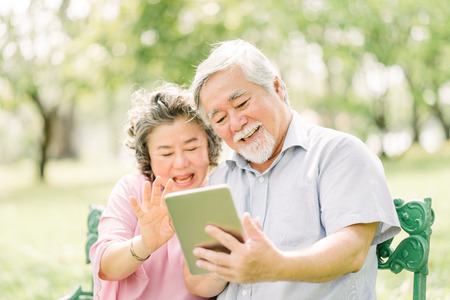 Happy and smile senior Asian couple using digital tablet together outdoor in park