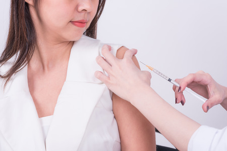 Close up of doctor hand using syringe to make vaccine injection to Asian female patient