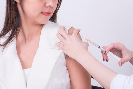 Schließen Sie oben von Doktorhand unter Verwendung der Spritze, um dem asiatischen weiblichen Patienten Impfstoffeinspritzung zu machen