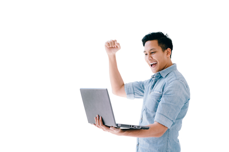 Happy excited Asian man holding laptop and raising his arm up to celebrate success or achievement isolated on white. Stockfoto