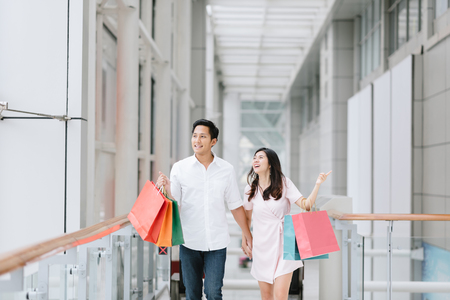 Happy Asian couple holding colorful shopping bags and enjoying shopping, having fun together in mall. Consumerism, love, dating, lifestyle concept