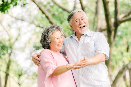 Happy senior Asian couple dancing in the park in sunny day Stockfoto