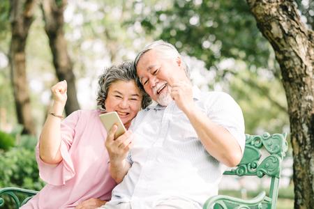 Gelukkig senior Aziatisch paar lachen en vieren succes samen met smartphon in park