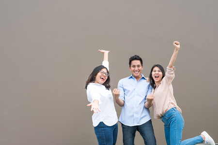 Grupo de tres amigos asiáticos felices en ropa casual de pie riendo y divirtiéndose juntos