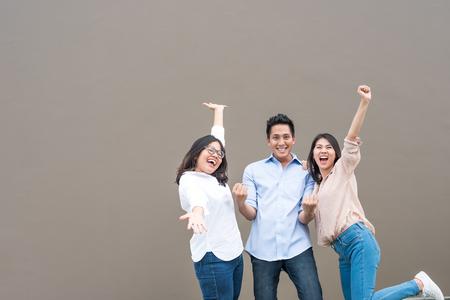Groupe de trois amis asiatiques heureux en tenue décontractée rire debout et s'amuser ensemble Banque d'images