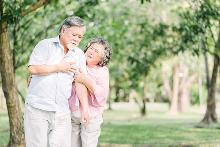 Senior Asian man holding his chest and feeling pain suffering from heart attack outdoor at the park while his wife feeling concern