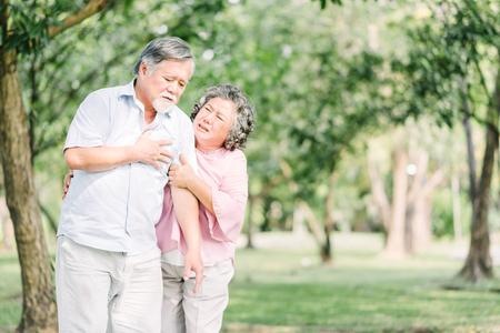 Uomo asiatico senior che tiene il suo petto e che sente dolore che soffre di attacco di cuore all'aperto al parco mentre sua moglie sente preoccupazione