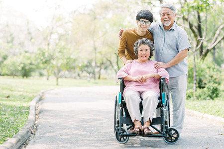 Happy Asian family, senior and young man, walking together in the park using wheelchair 版權商用圖片