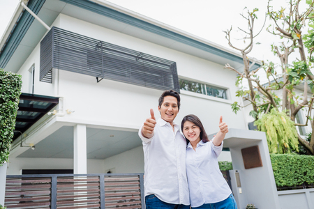Glückliches asiatisches Paar mit dem Daumen oben, das zusammen vor ihrem Haus steht Standard-Bild