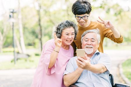 Familia de ancianos asiáticos feliz divirtiéndose con el teléfono inteligente en el parque