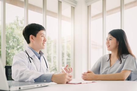 사무실에서 젊은 여성 환자와 상담하는 아시아 의사