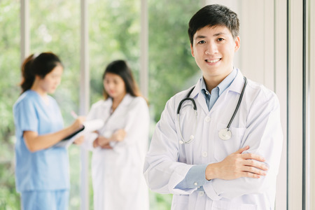 Attractive young confident Asian male doctor in front of medical staffs in background