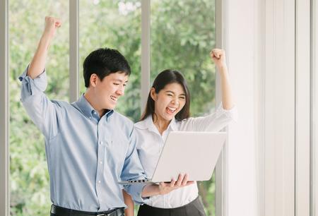Jong Aziatisch stel dat succes viert met armen omhoog terwijl ze binnen op de laptop zitten