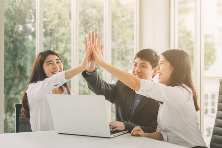 Gropu of young Asian business people giving high five to celebrate success on working project in meeting room Banco de Imagens