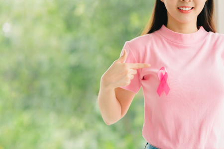 Happy young woman in pink shirt pointing at pink breast cancer awareness ribbon Banco de Imagens