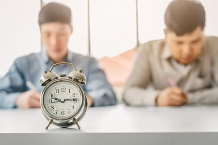 Vintage alarm clock with men doing test or paper work in background