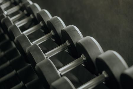 Row of dumbbells on rack in fitness gym Banco de Imagens