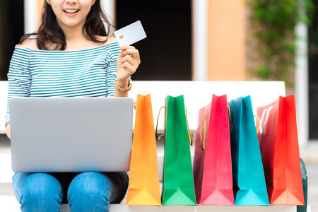 Cropped image of smile woman enjoy shopping online holding credit card with shopping bag Banco de Imagens