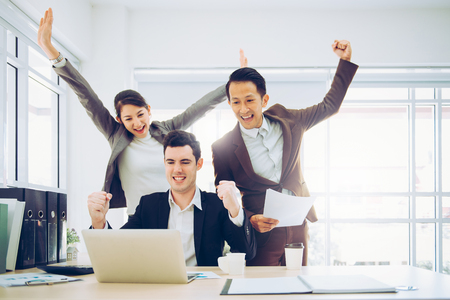 Business people team celebrated success with arm up while watching something in laptop screen in office