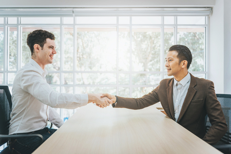 Two happy businessmen shaking hands in an office. Focus on hand