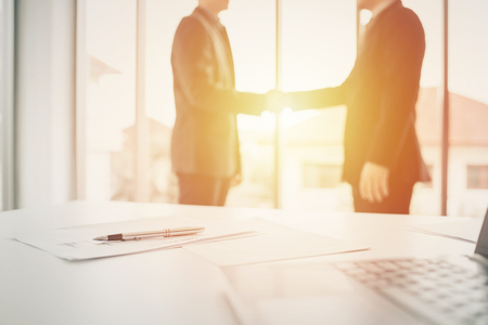 Businessman shaking hands for partnership and agreement in meeting room. Focused on pen Banco de Imagens