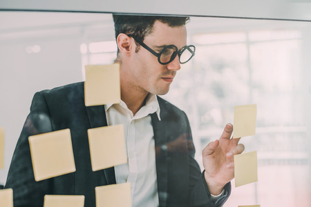 Businessman planning with sticky notes on a glass board