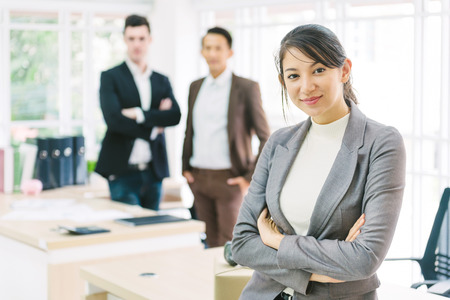 Cofident beautiful business woman in office with businessmen in background Banco de Imagens