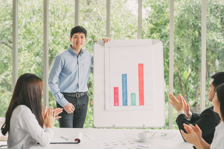 Confident young man standing next to flipchart and smiling while his colleagues giving applauding