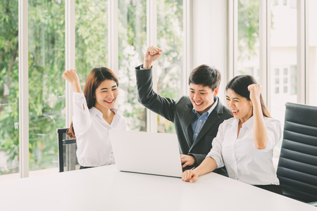 Group of youngzAsian business people celebrate success with laptop Stock Photo