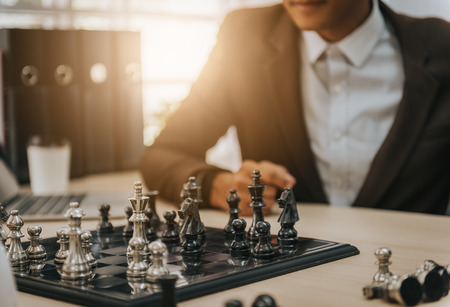 Cofident business man playing chess. business strategic concept