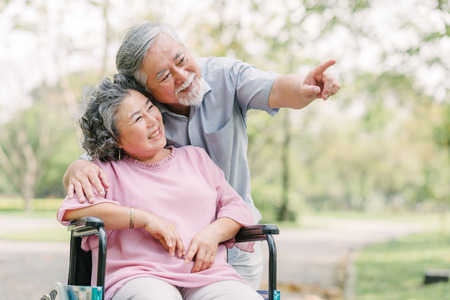 Happy Asian senior couple smiling outside in the park while woman sitting in wheelchair